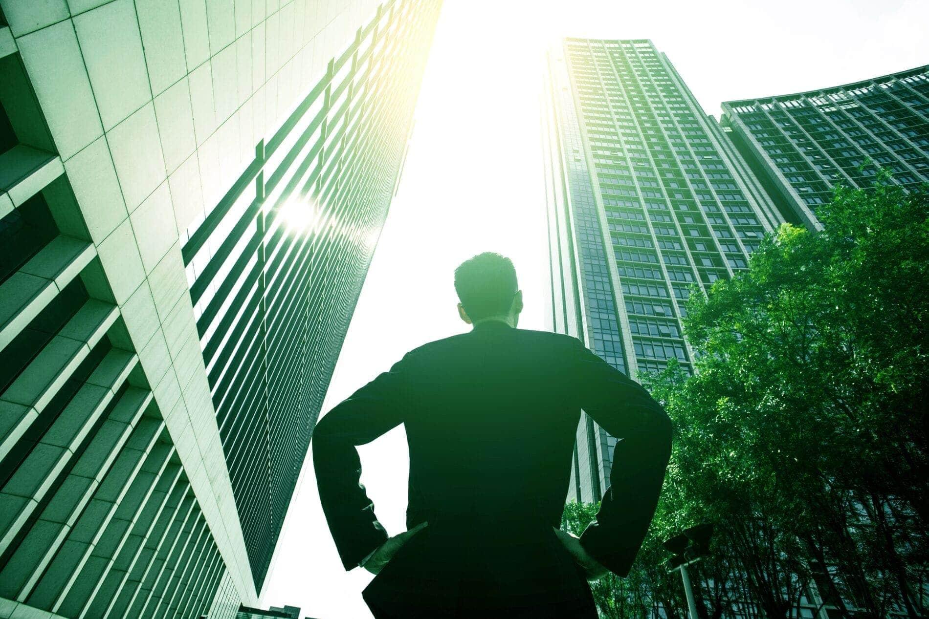 Un homme qui regarde en l'air vers des gratte-ciel