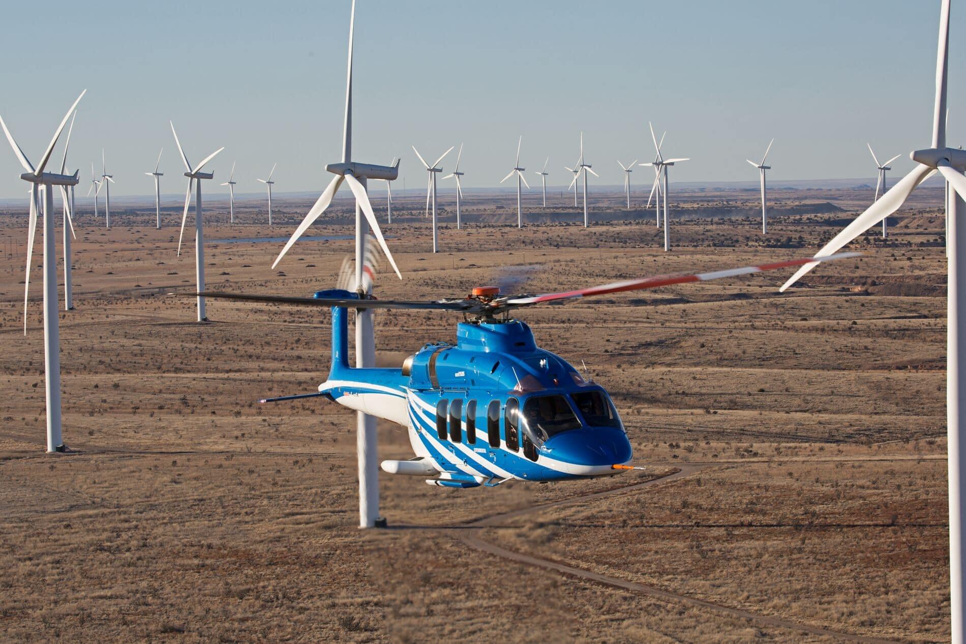 Bell 525 volant au travers d'un parc éolien en milieu désertique